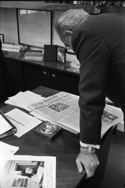 President Lyndon B. Johnson reading newspaper headline re bombing halt