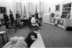 President Lyndon B. Johnson, family members, and staff watching the President's announcement of bombing halt on television