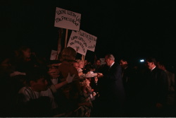 Supporting the Vietnam War: President Lyndon B. Johnson shakes hands with crowd, some carrying signs of support for LBJ